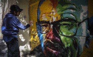 El artista AXE Colours repintando el grafiti de Walter White (Breaking bad), en la calle Verntallat, 12, en el barrio de Gràcia (Barcelona).