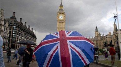 Un transe�nte se refugia de la lluvia en un paraguas con la bandera brit�nica, cerca del Big Ben, este s�bado.