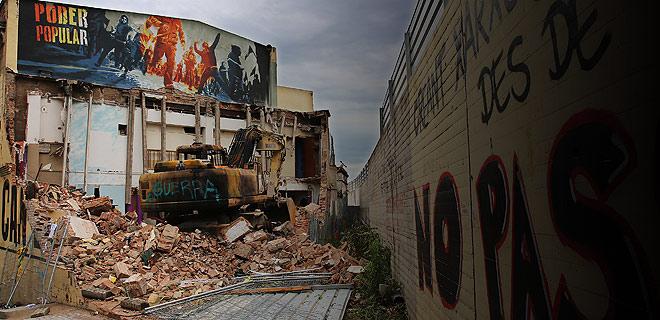 Una excavadora, sobre los restos del edificio demolido del centro social de Can Vies.