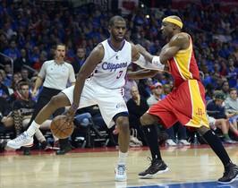 Chris Paul, de los Clippers, da un pase atrás bajo las piernas ante Jason Terry, de los Rockets.