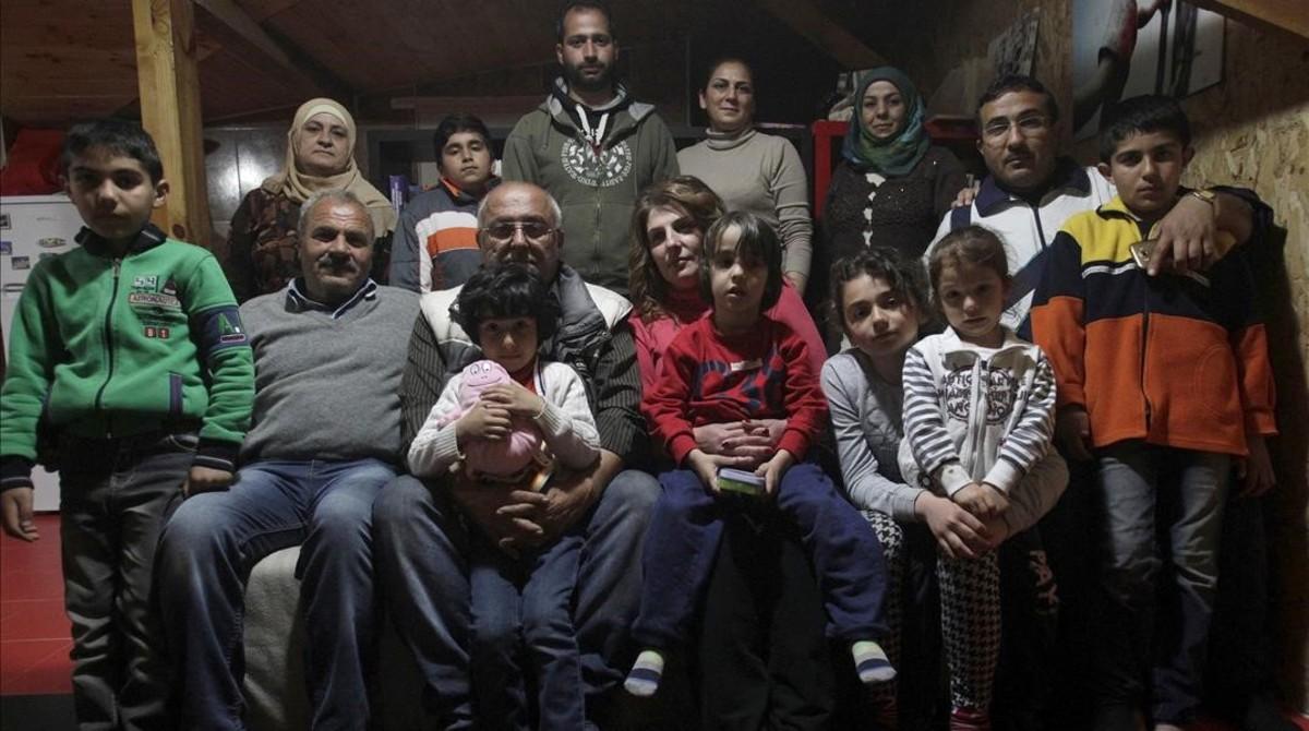 Dimitris Spiridis (en primera fila, tercero por la izquierda), junto a su mujer, Maria, y varios miembros de las dos familias sirias que acoge en su casa, en Evropos, cerca de Idomeni, este lunes.