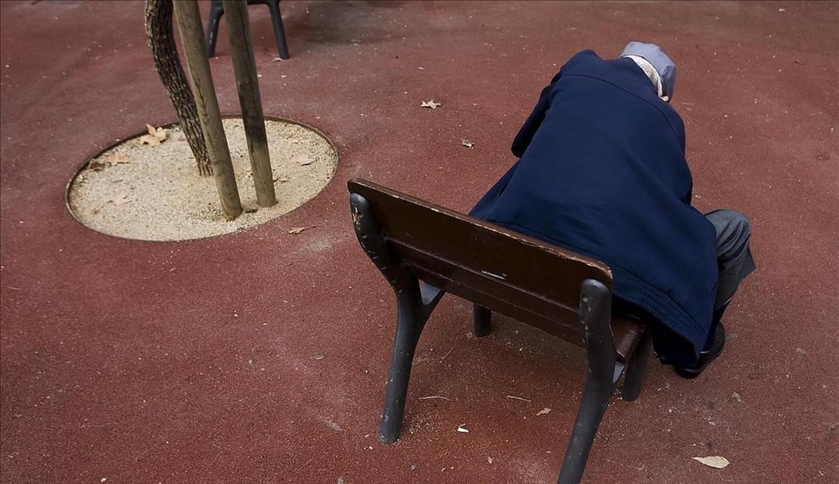 Un anciano, sentado solo en el banco de un parque de Barcelona.