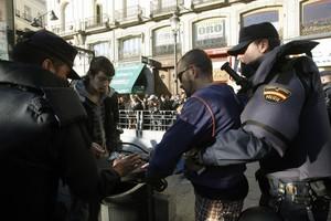 Un policía cachea una persona