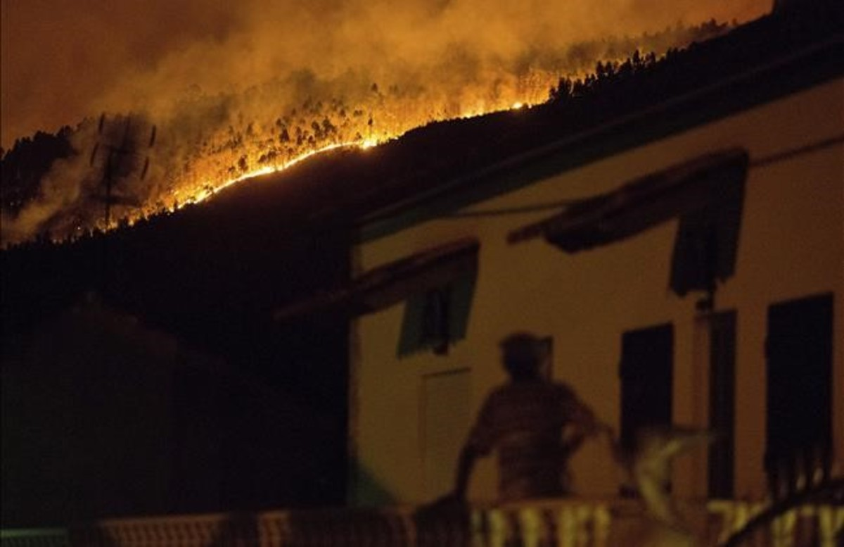 abertran38938929 a man on the balcony of a house looks up at a forest fire ra170618115500