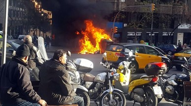 Contenedores ardiendo en el cruce de Secretari Coloma con Pi i Margall, en Gràcia, este jueves.