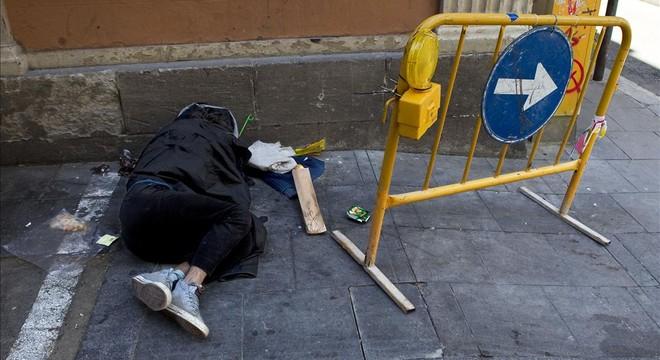 Un indigente duerme en plena calle en Barcelona.