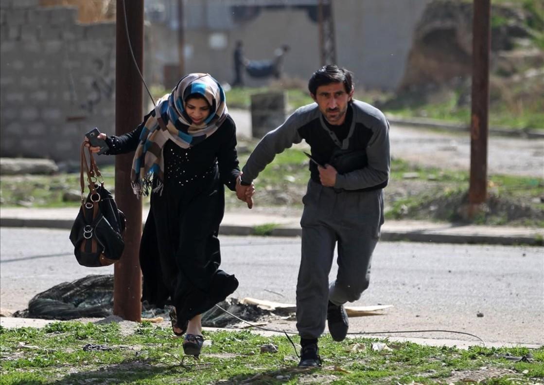 Una pareja corre para protegerse de una ofensiva militar el el barrio de Al-Tayaran de Mosul, Irak.