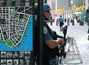 Un agent vigila la Piscina Sud al recinte del World Trade Center, ahir. A la dreta, policies al metro i a prop de la borsa.