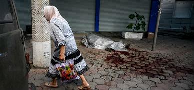 Una mujer camina junto a un cad�ver en Donetsk.
