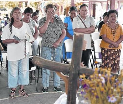 Los padres de los estudiantes asesinados rezan frente a un altar erigido en Ayotzinapa, en memoria de las víctimas de la matanza.