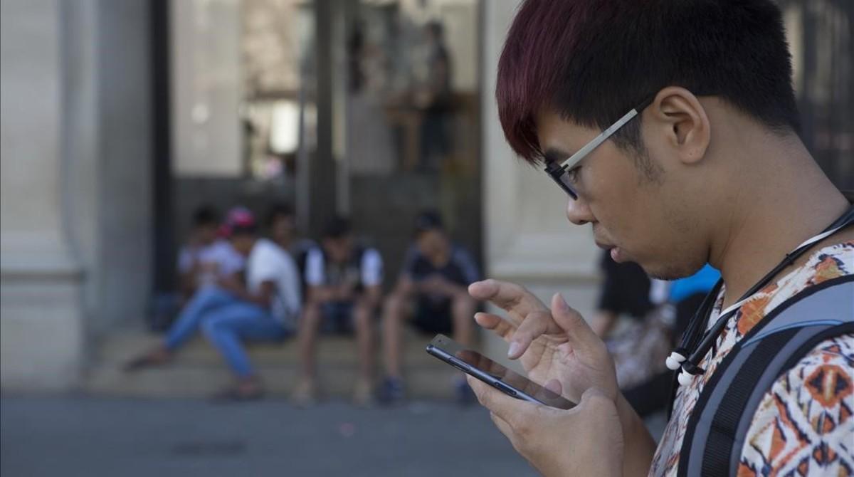 Usuarios de móviles en el paseo de Gràcia de Barcelona.