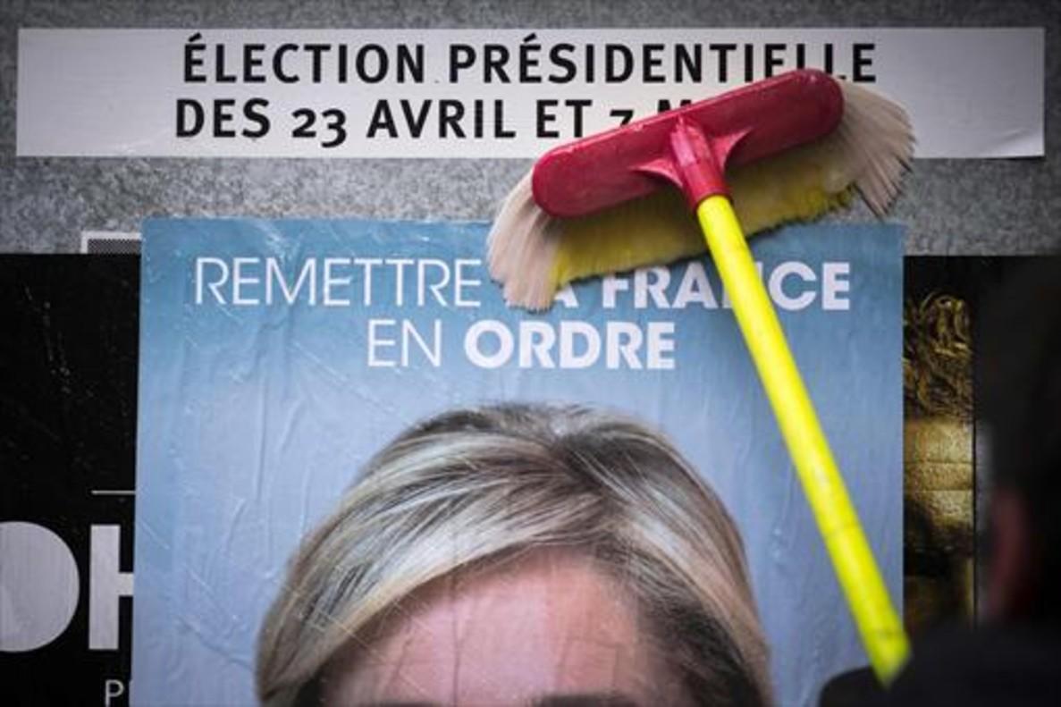 Un empleado del Frente Nacional pega un cartel electoral de Marine Le Pen al inicio de la campaña.