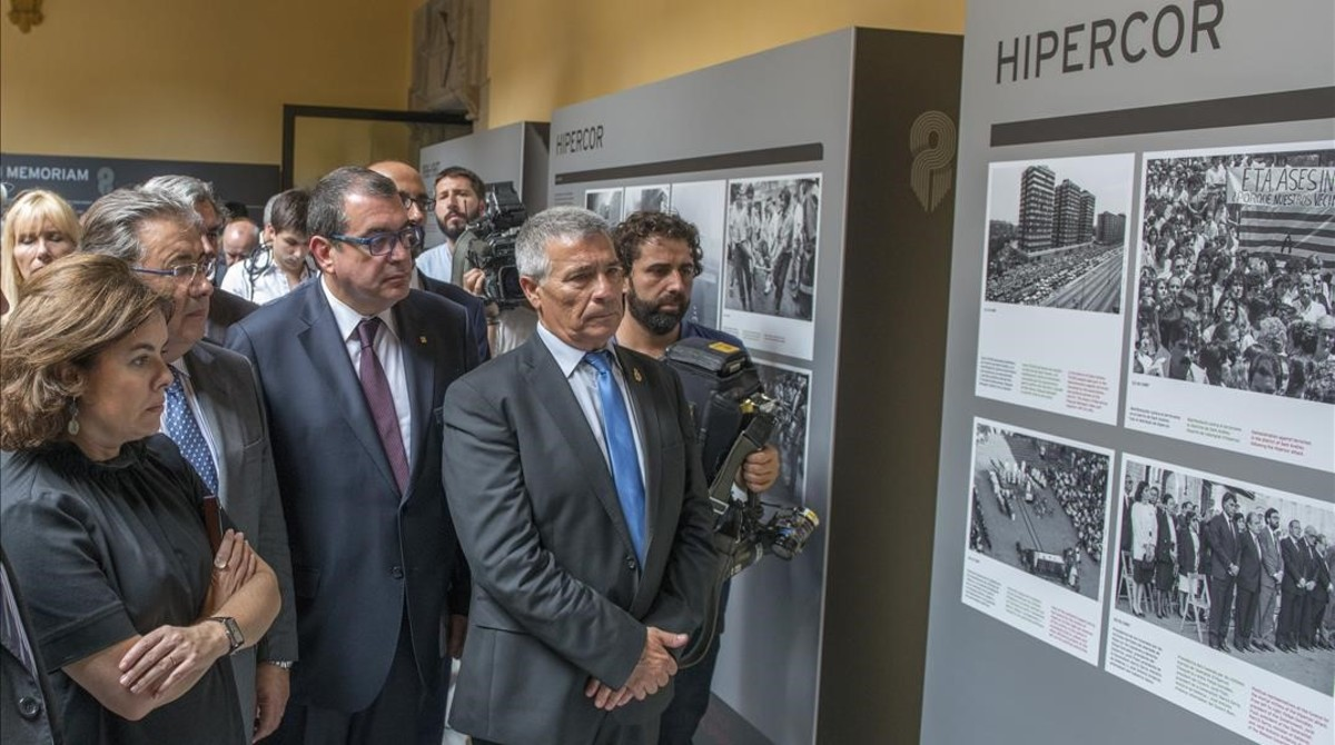 La vicepresidenta Soraya Sáenz de Santamaría, el ministro Juan Ignacio Zoido, el conseller Jordi Jané y el presidente de la ACVOT, José Vargas, este lunes, en la exposición sobre el atentado de Hipercor.