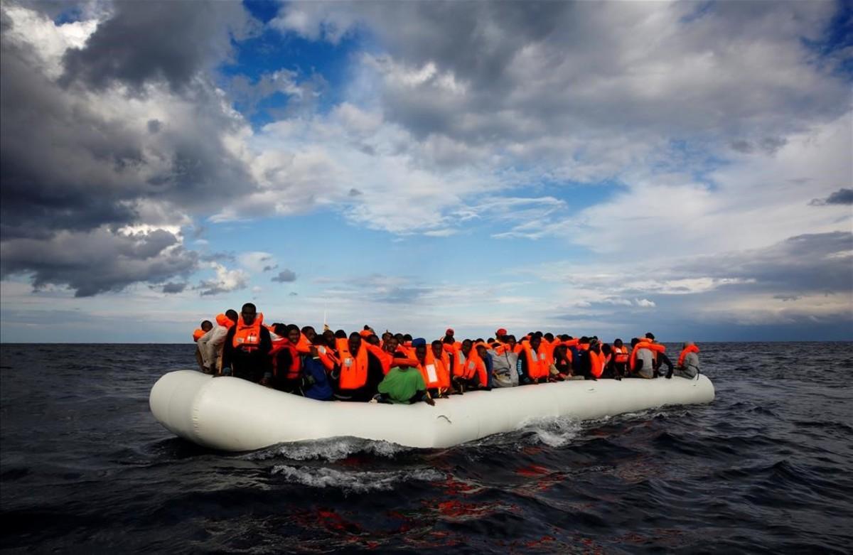 Una balsa con inmigrantes a laderiva en el Mediterráneo frente ala costa libia antes de ser rescatados por la ONG Proactiva Open Arms.