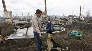 Una familia regresa a su casa tras los incendios forestales en el asentamiento siberiano de Strelka, Rusia.