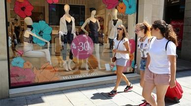 Varias jóvenes pasan frente a una tienda con descuentos en Barcelona.