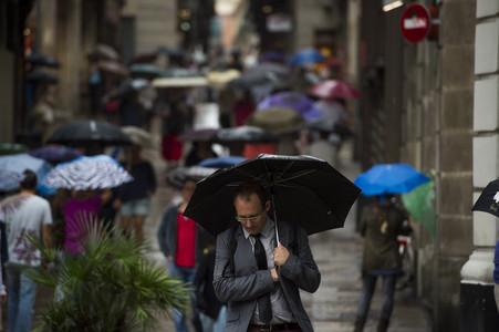 Vianants es protegeixen de la pluja amb paraigües pels carrers del barri gòtic el setembre passat