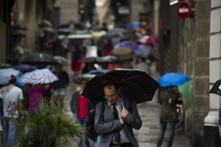 Viandantes se protegen de la lluvia con paraguas por las calles del barrio Gòtic, en una imagen de archivo.