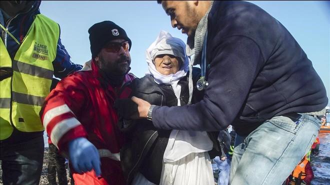 Voluntarios ayudan a una mujer anciana de Afganist�n tras desembarcar con otros refugiados en Skala Sykaminias, en Lesbos, este mi�rcoles.