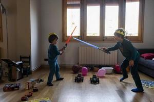 Guerreros 8 Los jedi Miquel y Mateu estrenan sus espadas láser en su piso de Barcelona, ayer.