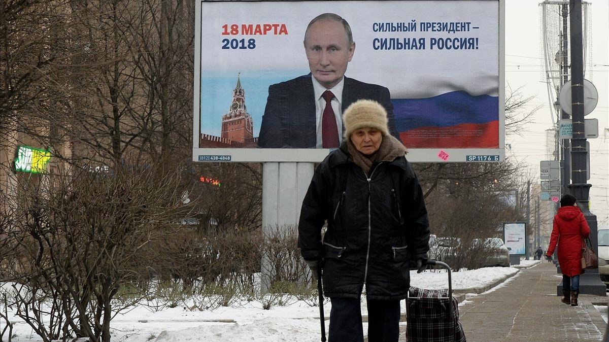 Una mujer pasa ante un espacio publicitario con la imagen de Putin y la leyenda Un presidente fuerte es un país fuerte, en San Petersburgo, el 12 de enero.