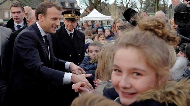 Macron saluda a los residentes a su llegada a un centro de migrantes en Croisilles, en el norte de Francia, el 16 de enero.