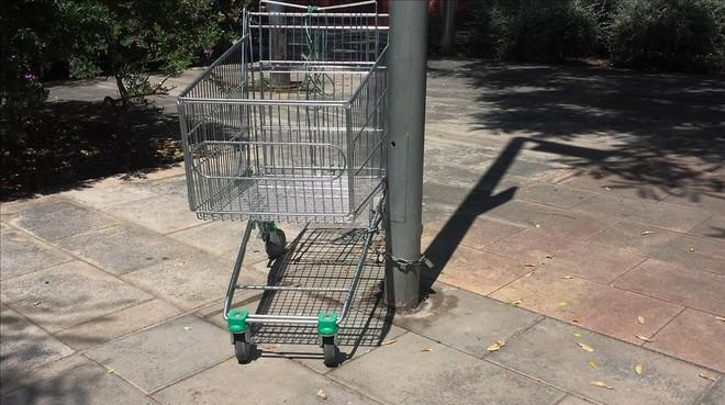 Un carro de supermercado, atado con un candado a una farola, en Barcelona.