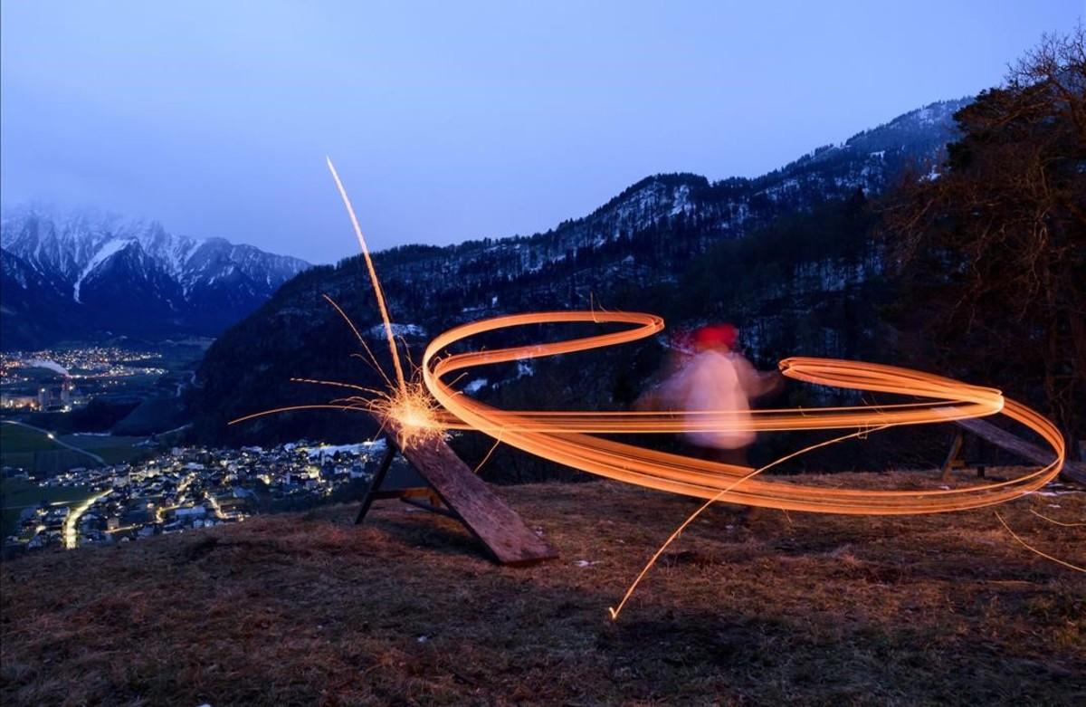 """Un nino lanza desde una montaña trozos de madera en llamas en la tradición llamada """"Schybaschlaha"""" y que supuestamente expulsa el invierno."""