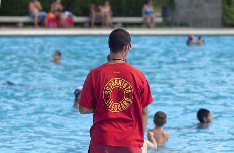 Un socorrista de la piscina de Can Dragó de Barcelona vigila las instalaciones tras el siniestro mortal.