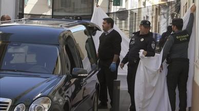 La policía oculta la salida de los cuerpos del domicilio en el momento de ser trasladados al coche funerario.