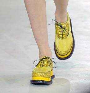 La comodidad en el calzado y el color amarillo, apuestas para la próxima temporada. Una modelo luce zapatos en el desfile de Jil Sander.