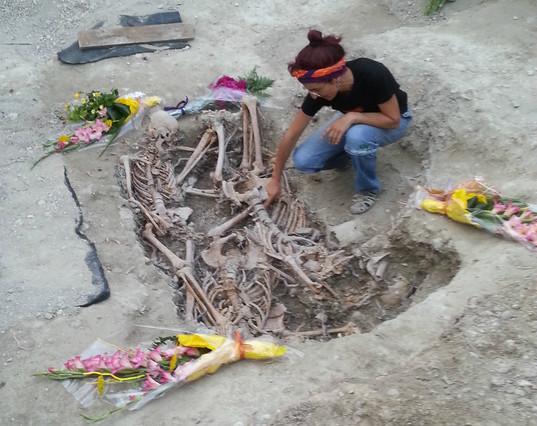 Una arqueóloga, ante los restos de los tres hombres.