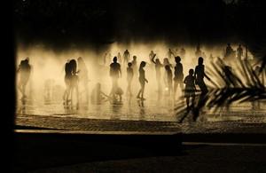 Gente refrescándose en unas fuentes al lado del río Manzanares, en Madrid.