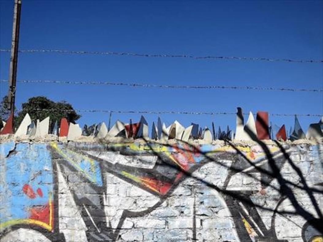 Un muro rematado con cristales en Bogotá.