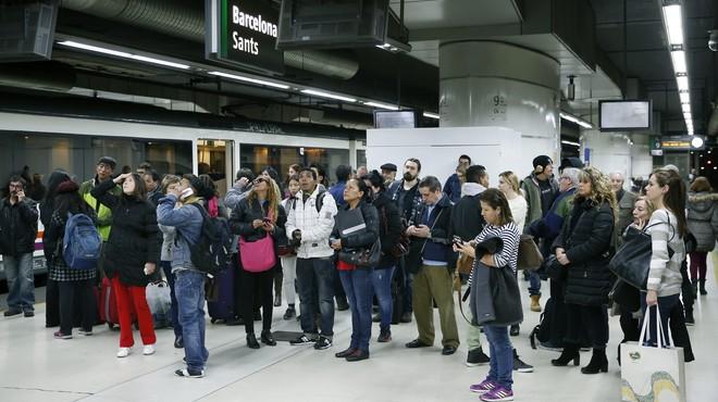Un grupo de viajeros observa los paneles informativos en la estaci�n de Sants de Barcelona.