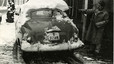 Un barcelonés, manguera en mano, trata de disolver la nieve del techo de su coche.
