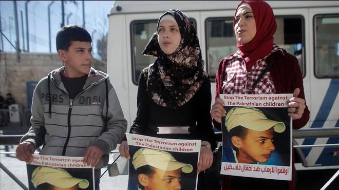 Los familiares del adolescente palestino Mohamed Abu Jdeir que muri� en 2014, muestran su retrato en el exterior de la Audiencia en Jerusal�n.