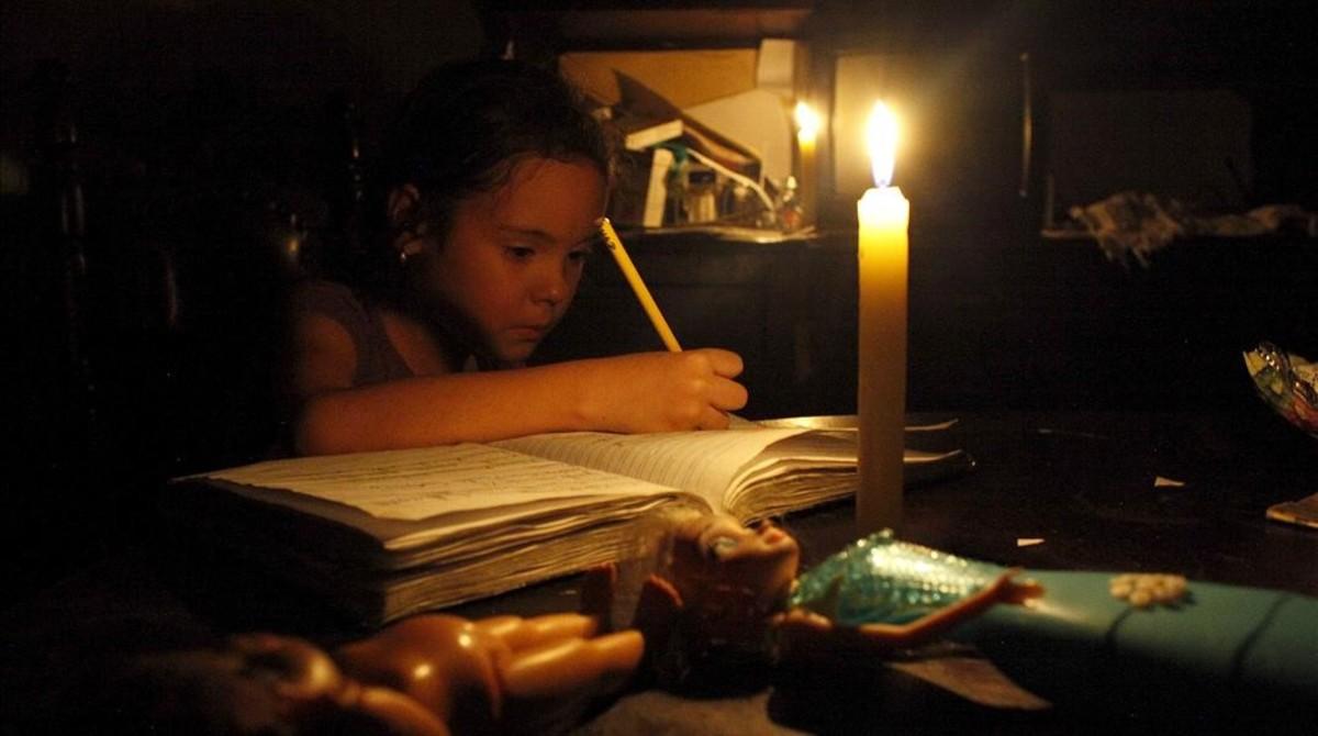 Una chica hace sus deberes a la luz de una vela, en San Cristóbal, en el estado de Tachira (Venezuela), el 25 de abril.