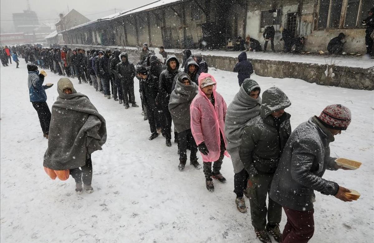 Inmigrantesrecibencomidaen el exterior de un almacén aduanero abandonado en Belgrado, Serbia.
