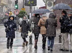Varias personas pasean por una céntrica calle de Granada durante un temporal de lluvia y frío del pasado invierno