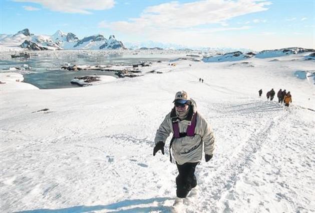 Unos turistas caminan por la Antártida.