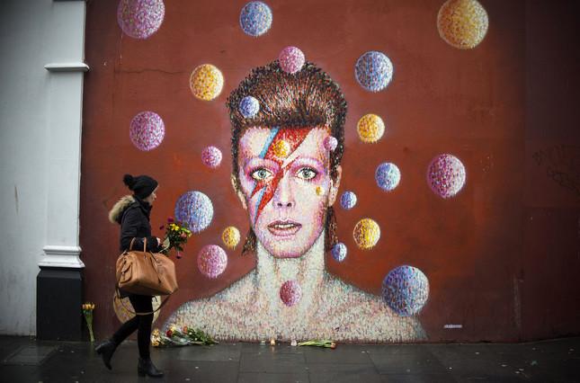 Una chica deposita flores frente a un mural de David Bowie en Brixton, Londres