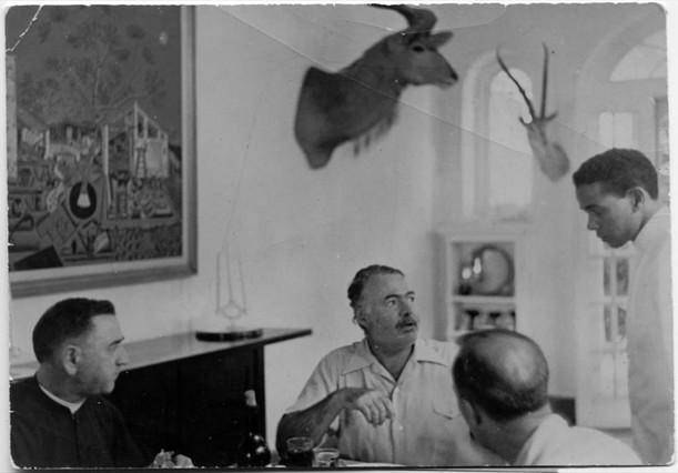 Ernest Hemingway con unos amigos en el comerdor de Finca Vig�a presidido por 'La mas�a'.