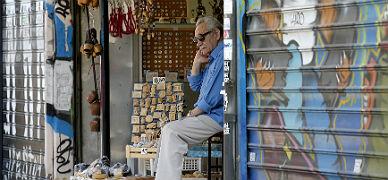 Un vendedor aguarda pacientemente la llegada de clientes en el �rea c�ntrica de Atenas.