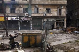 Un rebelde sirio apunta con su arma tras una barricada en una calle de la ciudad de Alepo, el s�bado.