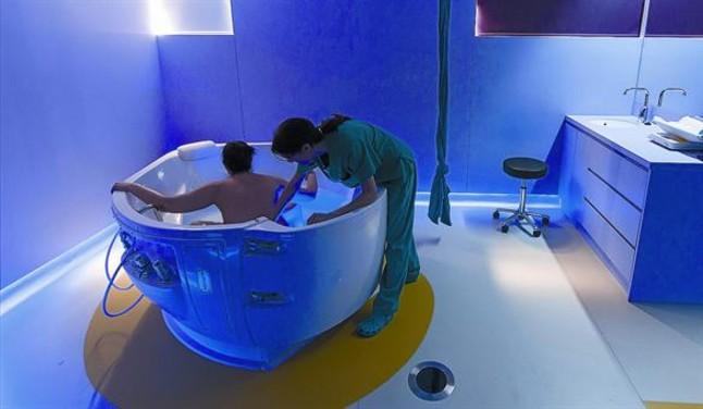 Una parturienta, en la bañera de la Maternitat del Clínic, asistida por una comadrona, ayer. FERRAN NADEU