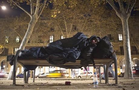 Una persona sin techo duerme en un banco junto a la Ciutadella.