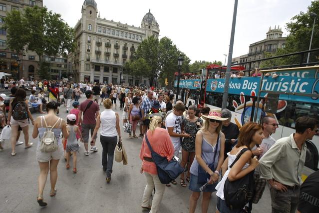 Grandes colas de visitantes para coger el Bus Turístic en plaza Catalunya.