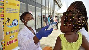 Una metgessa pren la temperatura a una dona i la seva filla, dijous, a laeroport de Bata (Guinea Equatorial).