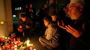 Un grupo reza frente a un altar con velas encendidas en memoria del niño inmigrante asesinado.